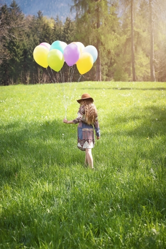 Girl in a field with ballons